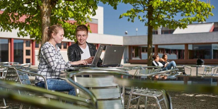 Eine Schülerin und ein Schüler unterhalten sich am Laptop.